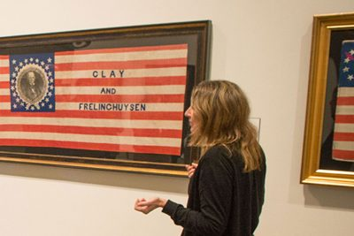 Nancy Stula, executive director, leads tour of the Mark and Rosalind Shenkman Collection of American Political Flags and Textiles on display at the William Benton Museum on Dec. 16, 2016