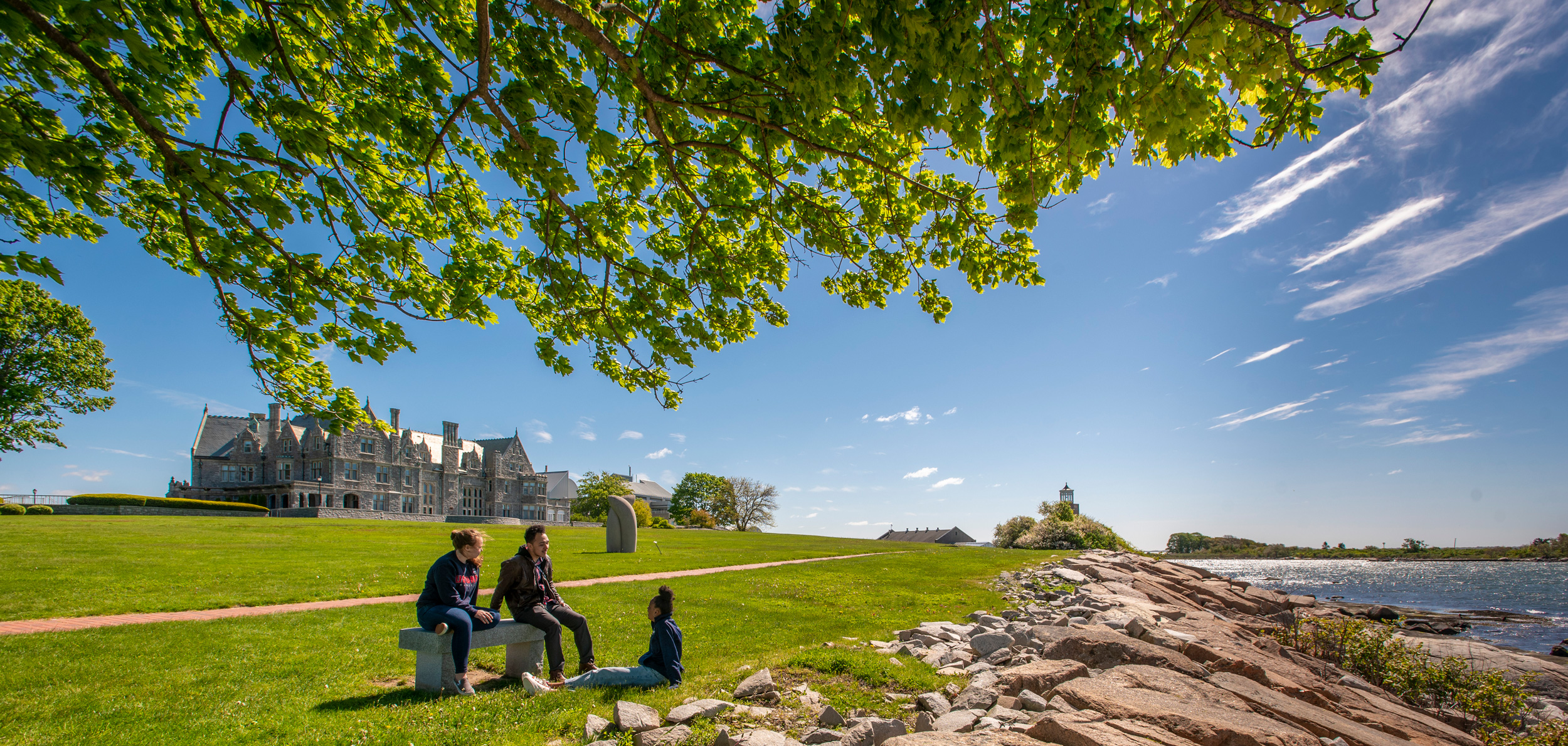 Students hanging out by the rocks on the Avery Point campus